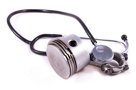 Internal combustion engine piston and medical stethoscope. Mechanical and automotive parts tested by medical devices. Light background.
