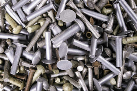 Various sizes of aluminum rivets. Accessories for joining machine parts stacked. Dark background.