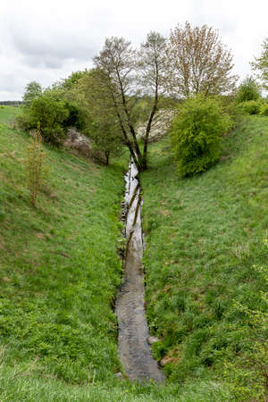 Water in a man-dug trench. Water drainage channel. Spring season.