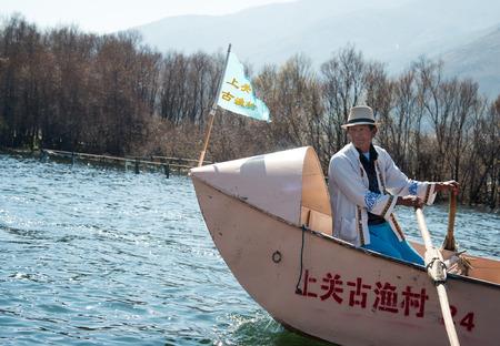 Old man rowing boat in Erhai lake