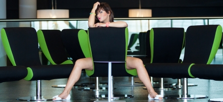 sits on a chair: young beautiful woman sits on chair in business room