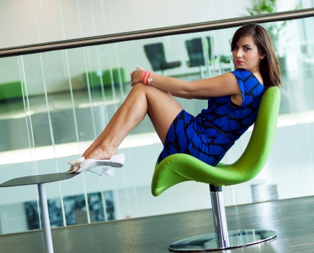 sits on a chair: young beautiful woman sits on green chair in business room Stock Photo