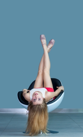 young attractive blonde girl lying on chair upside down photo