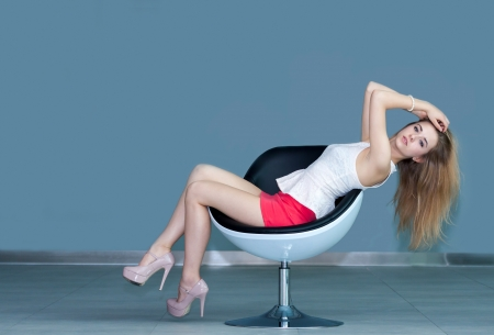 young attractive blonde girl sitting on chair and touching her hair