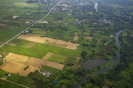 Farmer field village with river and road from top view