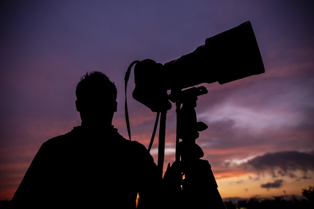 Silhouette of photographer with super telephoto lens and camera on tripod with beautiful twilight sky background