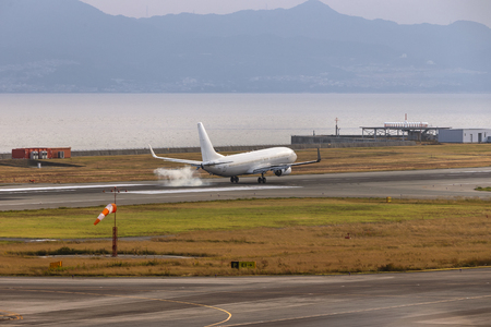 A white airplane landing touch down at Osaka airport, Japan beside the sea and mountain