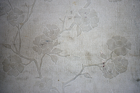 Dirty and aged white wall paper with rose flower pattern emboss