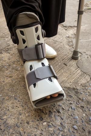 Una persona con zapato ortopédico y bastón.