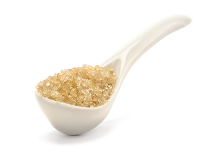 A brown sugar in the ceramic spoon isolated on white background
