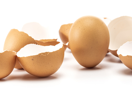 One egg stand up while other has cracked isolated on white background