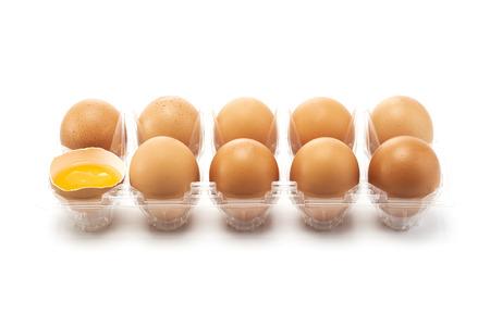 Eine Eierverpackung mit einem Eisprung links auf weißem Hintergrund