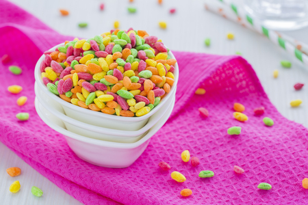 dishcloth: Colorful Rice Cereal on the pink dishcloth with glass of water and straws