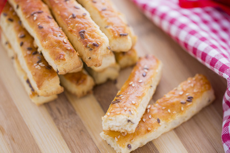 new years day: Bread Salty Grissini Sticks with sesame and flax seeds prepared for New Years Day with red ribbon and red Christmas decorations Stock Photo