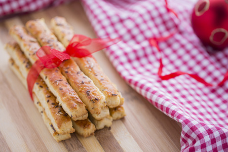 new years day: Bread Salty Sticks with sesame and flax seeds prepared for New Years Day with red ribbon and red Christmas decorations