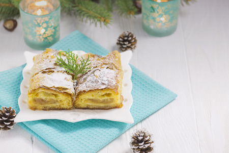 pinecones: Apple Pie on White Wood Table with Turquoise Cloth, Candles, Pinecones and Christmas Tree Decorations Stock Photo