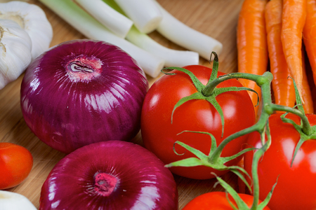 scallion: Red onion, carrots, green onion, scallion, tomatos and red pepper on a wooden board Stock Photo