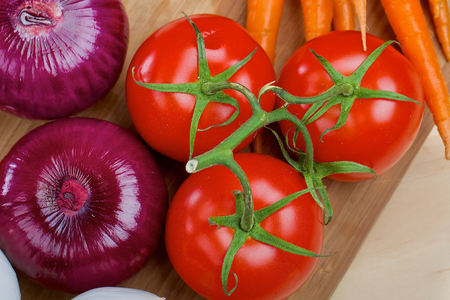 tomatos: Tomatos and purple onions on a wooden table