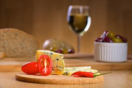 tabla de quesos: Queso azul con un vaso de vino y aceitunas en un fondo