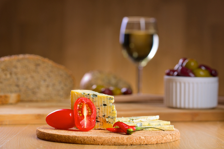 Blue cheese with glass of wine and olives on a background photo