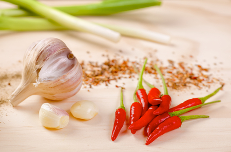 scallion: Red hot chilli peppers with a scallion and garlic on a wooden board