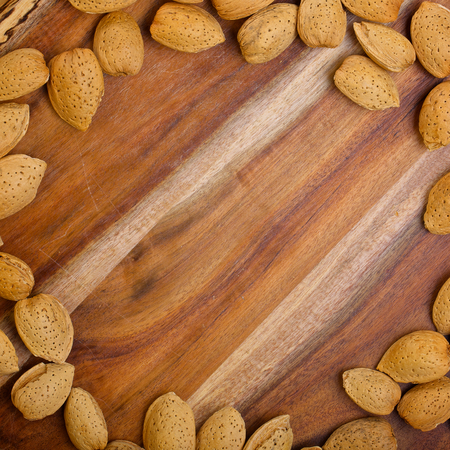 bordering: Almonds in shells bordering wooden table. Space for text