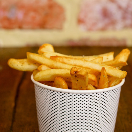 frites: Potatoes fries in a white paper bag on wooden board