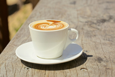 Cappuchino or latte coffe in a white cup with heart shaped foam Stock Photo