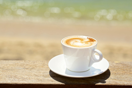 stiring: Cappuchino or latte coffe in a white cup with heart shaped foam Stock Photo