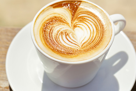 capucinno: Cappuchino or latte coffe in a white cup with heart shaped foam Stock Photo