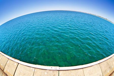 horison: Pier in green ocean water with fisheye horison