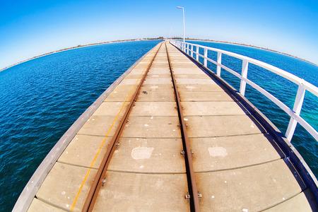 horison: Pier in blue ocean water with fisheye horison. Basselton jetty