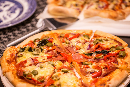 unsliced: Homemade pizza on white table Stock Photo