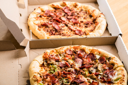 unsliced: Homemade pepperoni pizza in carton boxes