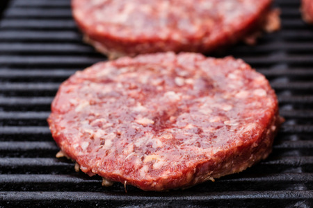 batch: a batch of grilled ground beef patties on BBQ