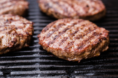 classic burger: Preparing a batch of  grilled ground beef patties or frikadeller on BBQ Stock Photo