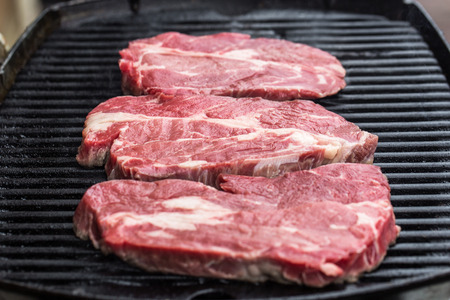 fryed: Raw fresh beef steaks being fryed or prepared on grill or BBQ Stock Photo
