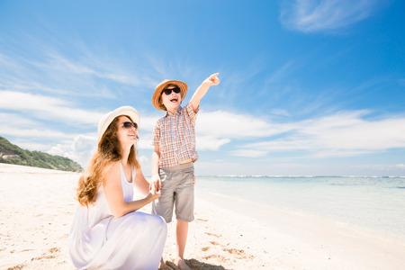 mama e hijo: Feliz bella joven madre e hijo disfrutando de tiempo en la playa con el cielo azul sobre el oc�ano en backgrund