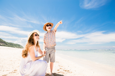 mother nature: Happy beautiful young mother and son enjoying beach time with blue sky over the ocean on backgrund