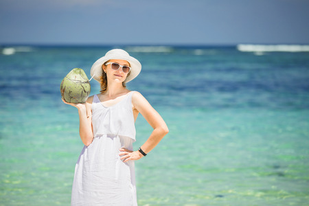 roo: Beautiful young woman holding and drinkind a coconut fresh cocktail in tropical sea Stock Photo