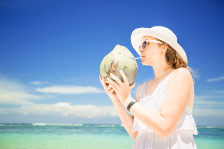 Beautiful young woman holding and drinkind a coconut fresh cocktail in tropical sea Stock Photo
