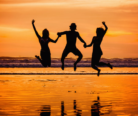 orenge: Silhouettes of happy young friends jumping on the beach  against red sunset Stock Photo