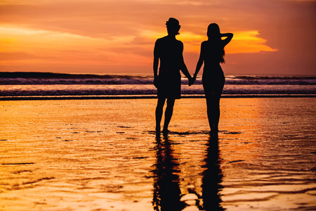 orenge: Silhouettes of young couple in love staing on the beach with beautiful red sunset as background