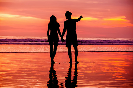 orenge: Silhouettes of young couple in love having a great time on the honeymoon staying on the beach with beautiful red sunset on background