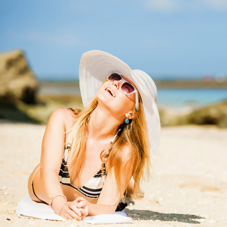 sunbath: Sexual happy blond girl with sunglasses and white hat take sunbath on the beach enjoying summer holidays. Travel, vacation, lifestyle concept. Squared