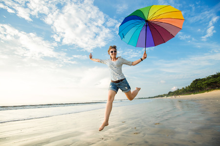 and fun: Cheerful young girl with rainbow umbrella having fun on the beach before sunset. Travel, holidays, vacation, healthy lifestyle concept Stock Photo