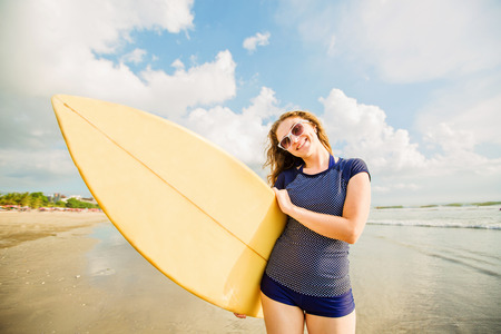 Beautiful young caucasian girl in rushwest and sunglasses with yellow surfboard at legian beach, Bali. Lyfestyle, leisure, sport, vacation, happines concept Stock Photo