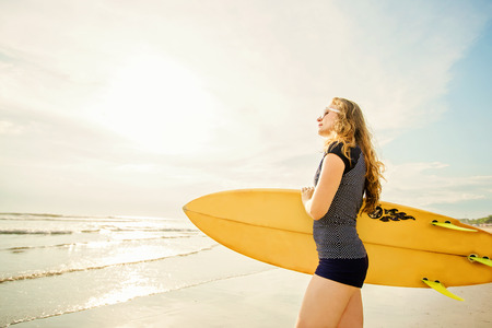 legian: Beautiful young caucasian girl in rushwest and sunglasses with yellow surfboard at legian beach, Bali. Lyfestyle, leisure, sport, vacation, happines concept Stock Photo