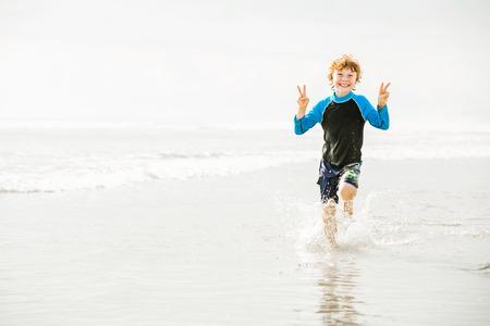 bali beach: Young boy in swimming shorts and rash vest runs along Bali beach near sunset