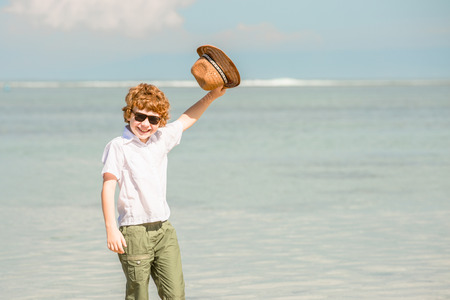 stays: Happy red haired kid boy wearing hipster sunglasses waving hat enjoying beautiful summer sunny day stays on the beach in shallow water Stock Photo